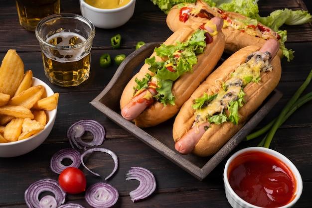 Alto ángulo de perros calientes con patatas y salsa de tomate