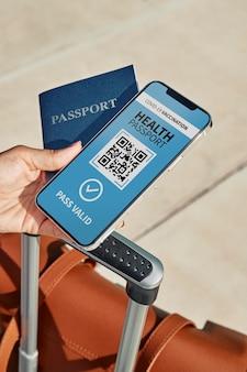 Alto ángulo de la persona que tiene un pasaporte de salud física y virtual en un teléfono inteligente