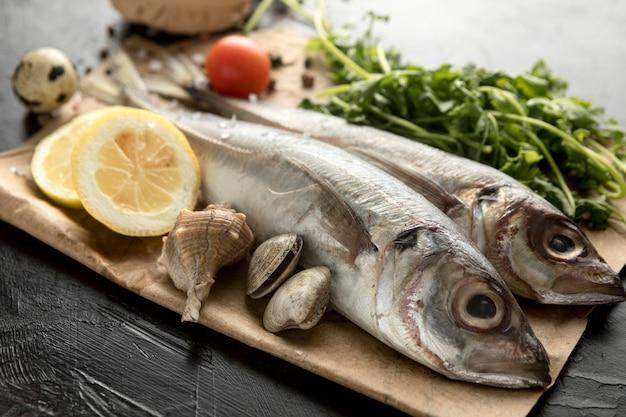 Alto ángulo de pescado con almejas y limón.