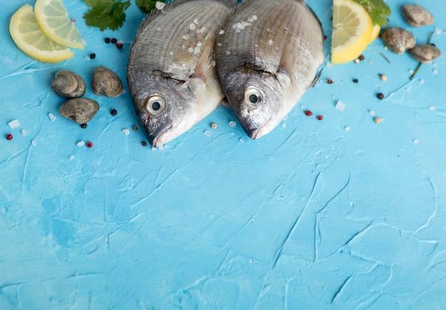 Alto ángulo de pescado con limón y copie el espacio