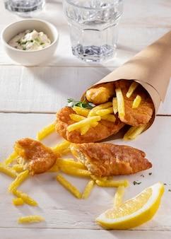 Alto ángulo de pescado y patatas fritas en cono de papel con rodaja de limón