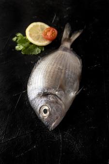 Alto ángulo de pescado con rodaja de limón y tomate