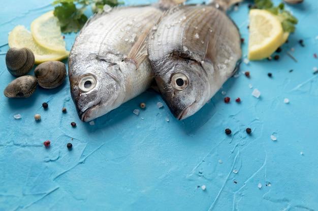 Alto ángulo de pescado con rodajas de limón y almejas