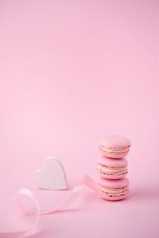Alto ángulo de pila de macarons con corazón y cinta