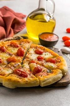 Alto ángulo de pizza cortada en rodajas con tomate y aceite