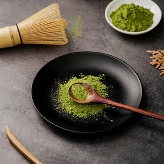 Alto ángulo de polvo de té matcha en plato con cuchara de madera