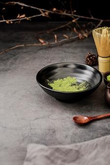 Alto ángulo de polvo de té matcha en un tazón con cuchara de madera