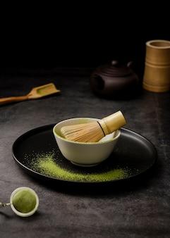 Alto ángulo de polvo de té matcha en un tazón con tamiz y placa
