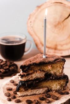Alto ángulo de rebanada de pastel con velas y café