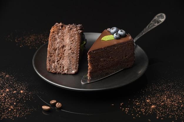 Alto ángulo de rebanadas de pastel de chocolate en un plato con espátula