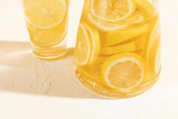 Alto ángulo de rodajas de limón fresco en vaso con limonada