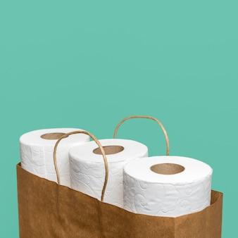 Alto ángulo de rollos de papel higiénico en bolsa de papel con espacio de copia