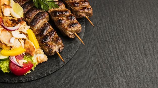 Alto ángulo de sabroso kebab en pizarra con espacio de copia