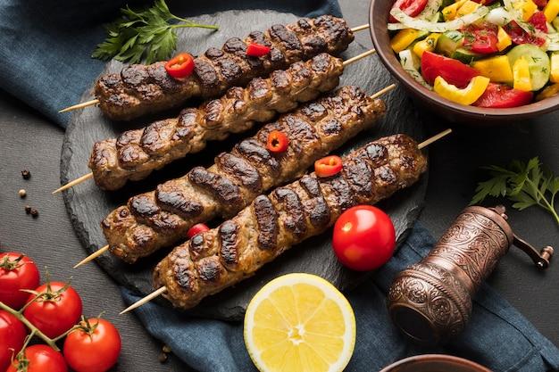 Alto ángulo de sabroso kebab en pizarra con otro plato y tomates