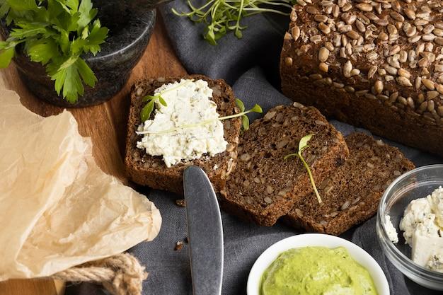 Alto ángulo de sándwich con cuchillo y hierbas.