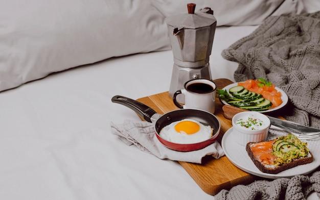 Alto ángulo de sándwiches de desayuno en la cama con huevo frito y espacio de copia