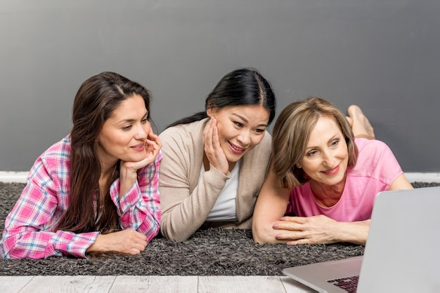 Alto ángulo smiley mujeres usando laptop