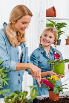 Alto ángulo sonriente madre e hija plantando flores
