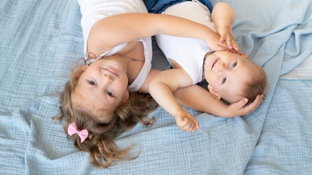 Alto ángulo sonriente niños sentados en la cama