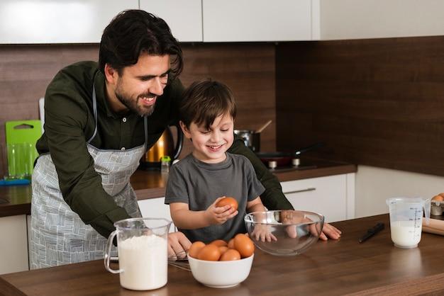 Alto ángulo sonriente padre e hijo cocinando