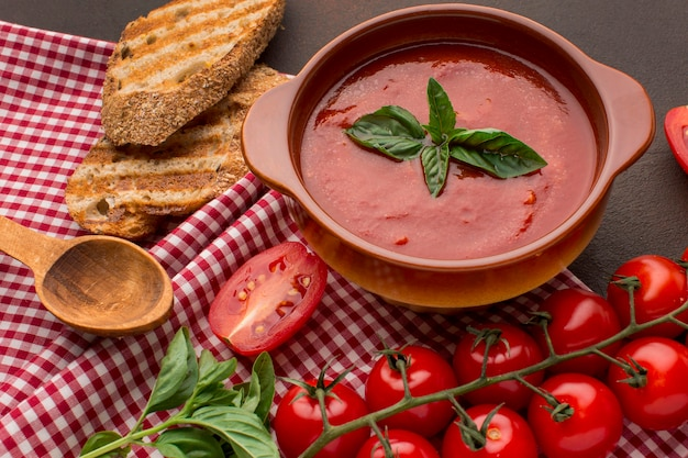 Alto ángulo de sopa de tomate de invierno en un tazón con tostadas y cuchara