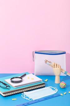 Alto ángulo de suministros para el regreso a la escuela con cuaderno y lupa