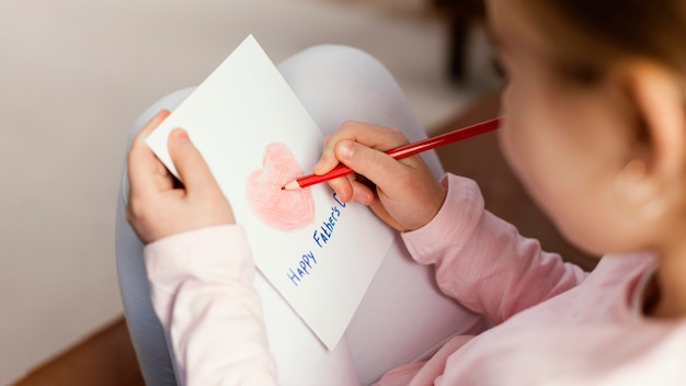 Alto ángulo de tarjeta de dibujo de hija para el día del padre