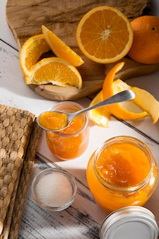 Alto ángulo de tarro de cristal transparente con mermelada de naranja