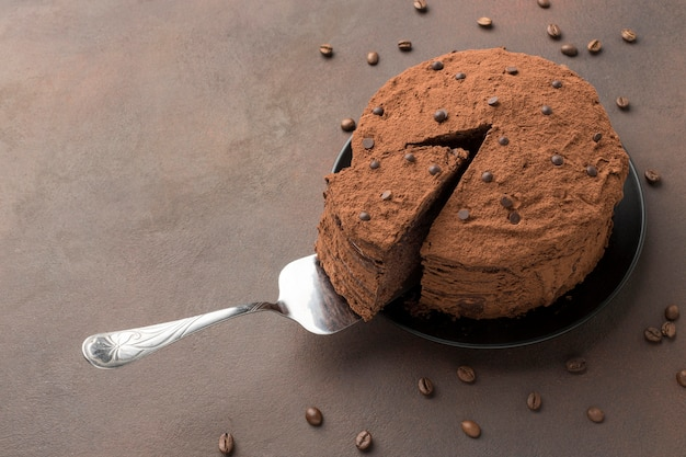 Alto ángulo de tarta de chocolate con cacao en polvo