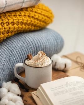 Alto ángulo de taza de café con crema batida y canela en rama