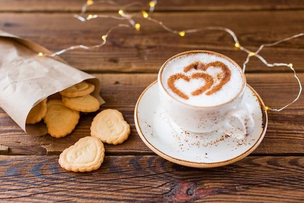 Alto ángulo de taza de café y galletas en forma de corazón.
