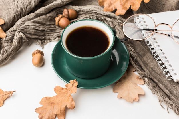 Alto ángulo de la taza de café con hojas de otoño y bellotas