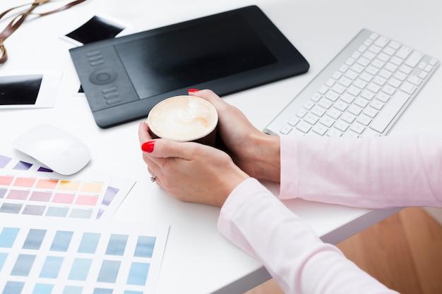 Alto ángulo de taza de café en manos de la mujer en el escritorio