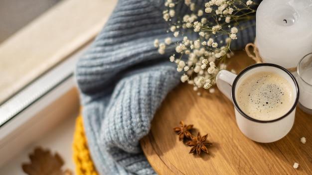 Alto ángulo de taza de café con suéter y hojas de otoño