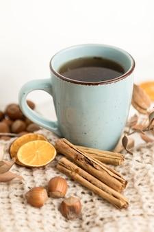 Alto ángulo de taza de té con castañas y ramas de canela