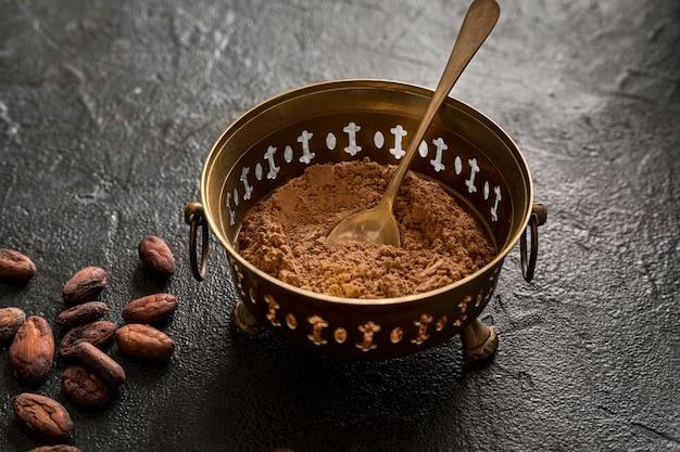 Alto ángulo del tazón con cacao en polvo y granos de cacao