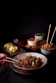 Alto ángulo de tazón de fideos con otra comida asiática