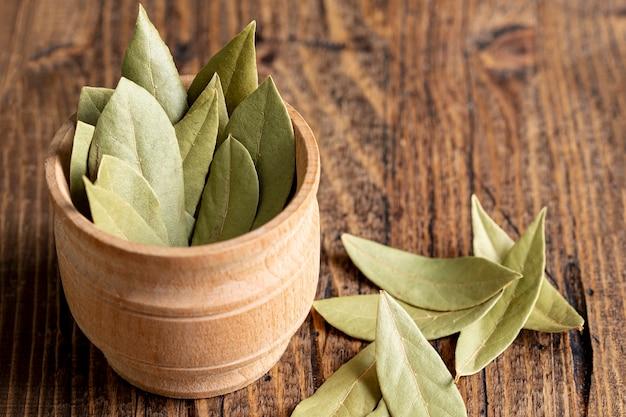 Alto ángulo de tazón de madera con hojas de laurel