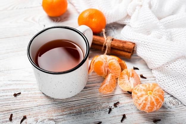 Alto ángulo de té caliente con mandarinas.