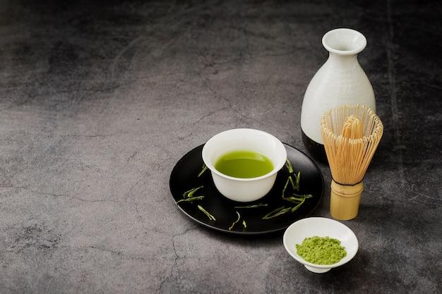 Alto ángulo de té matcha en taza en plato