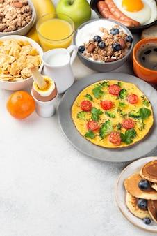 Alto ángulo de tortilla con cereales y panqueques para el desayuno.