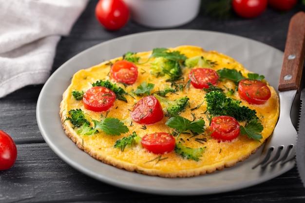 Alto ángulo de tortilla para el desayuno con tomates y hierbas.