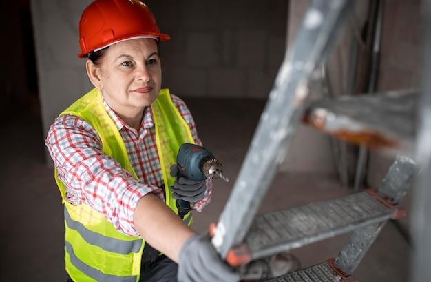 Alto ángulo de trabajadora de la construcción con taladro eléctrico