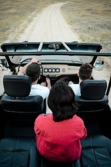 Alto ángulo de tres amigos viajando juntos en coche