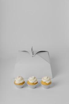 Alto ángulo de tres cupcakes con caja y espacio de copia