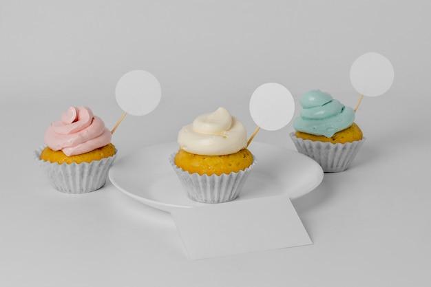 Alto ángulo de tres cupcakes con embalaje