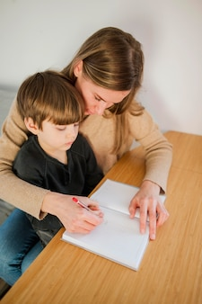 Alto ángulo de tutor femenino enseñando a niño en casa