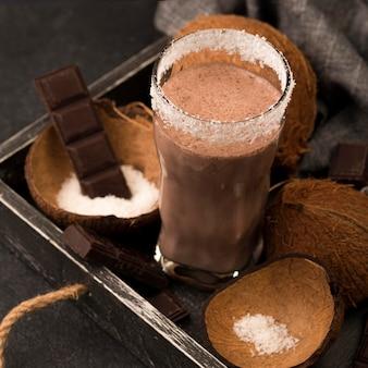 Alto ángulo de vaso de batido en bandeja con coco y chocolate