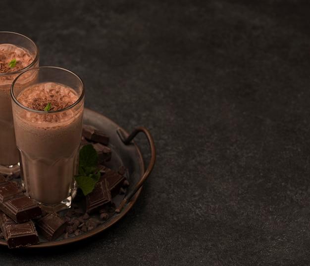 Alto ángulo de vasos de batido en bandeja con chocolate y copie el espacio