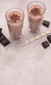 Alto ángulo de vasos de batido con chocolate y copie el espacio